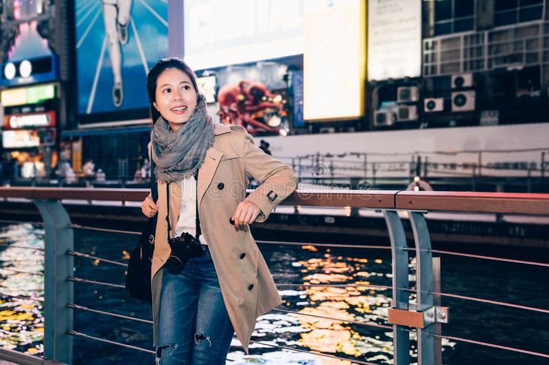 Girl tourist standing relaxing next to the river. Elegant office lady carry slr camera sightseeing dotonbori osaka japan in her business travel trip free time stock photography
