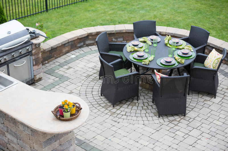 Elegant outdoor living space. On a paved brick patio with a summer kitchen and barbecue and a table laid with formal place settings for dinner, high angle view stock photo