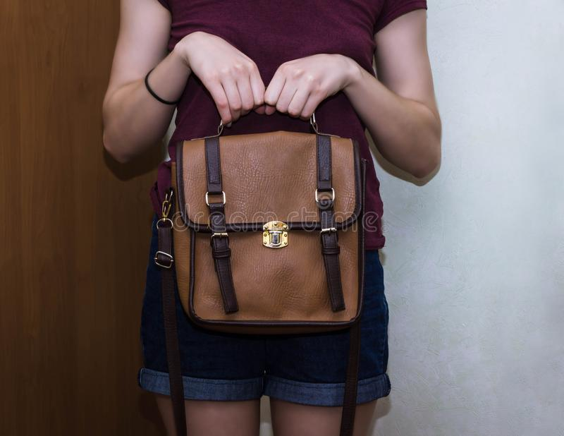 Elegant outfit. Closeup of brown leather bag handbag in hand of stylish woman fashionable girl royalty free stock photos