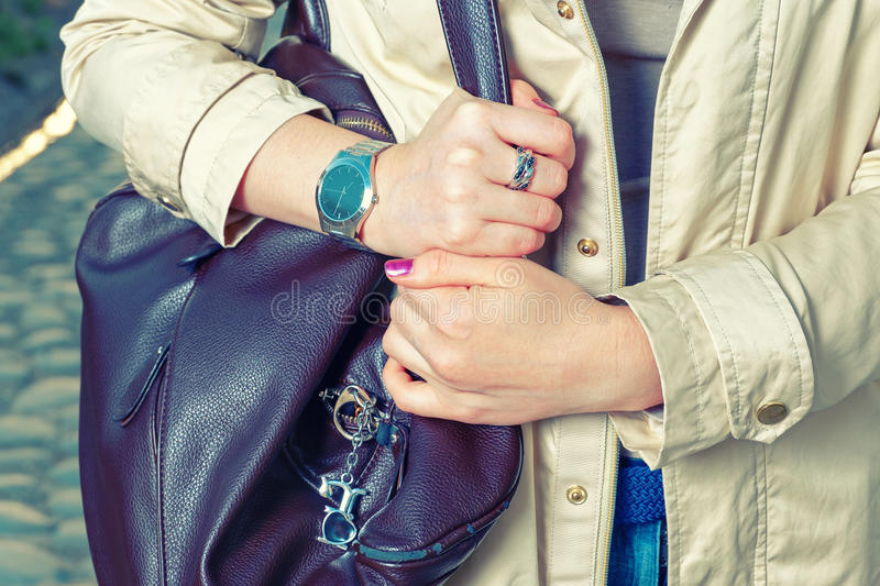 Elegant outfit. Closeup of brown leather bag handbag in hand of stylish woman. Fashionable girl in the street. Casual stock photography