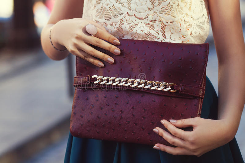 Elegant outfit. Closeup. Leather bag in hands of stylish woman. Fashionable girl on the street. Female fashion. royalty free stock photo