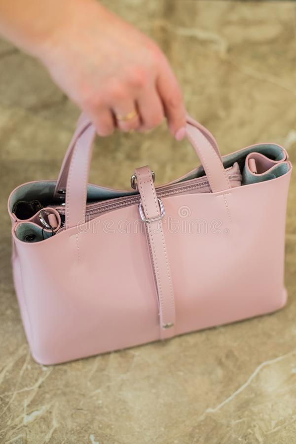 Elegant outfit. Closeup of pink powdery leather bag handbag in hand of stylish woman fashionable girl. Female fashion. royalty free stock images
