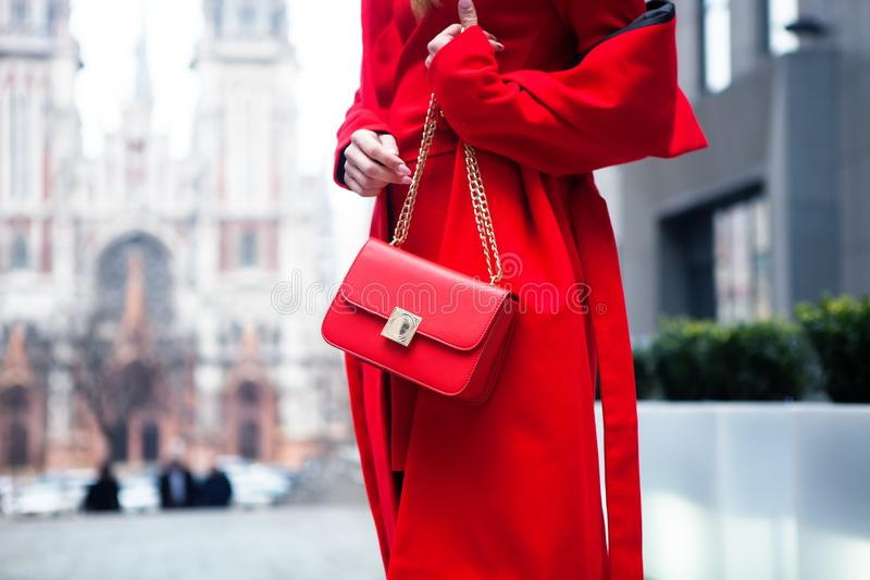Elegant outfit. Closeup of red leather bag in hands of stylish woman. Fashionable girl on the street. Female fashion. City lifesty royalty free stock photo