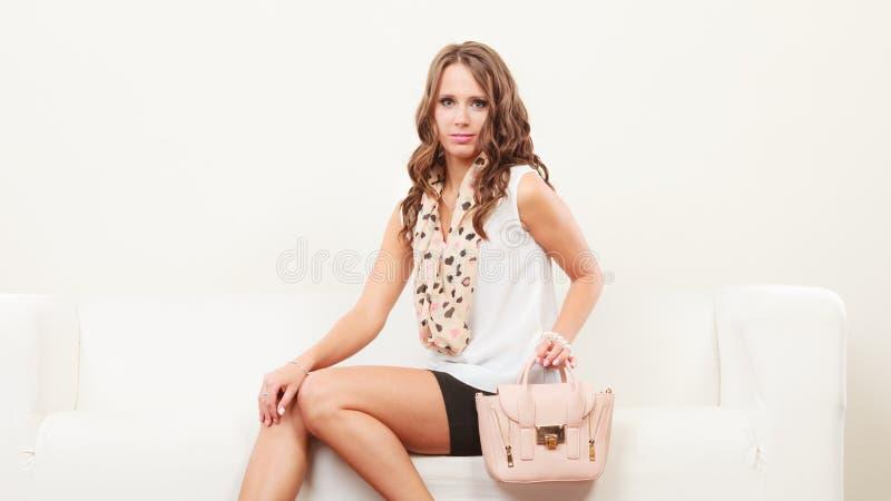 Fashionable girl with handbag sitting on sofa royalty free stock photography