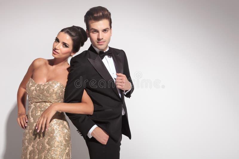 Elegant paar die terwijl het houden van wapens stellen stock foto's