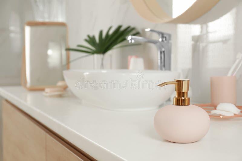 Elegant pink dispenser on countertop in bathroom interior. Elegant pink dispenser on light countertop in bathroom interior royalty free stock photo