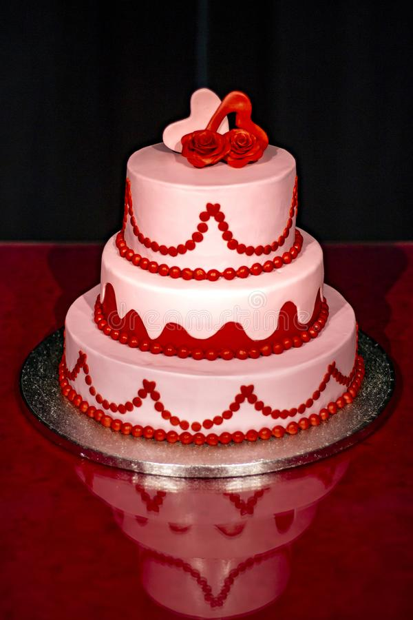 Elegant pink wedding cake decorated with red and pink roses and hearts stock photography