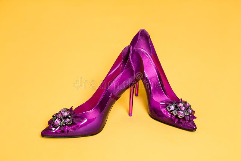 Elegant women`s shoes with high heel and glamor decorations on a yellow background stock photos