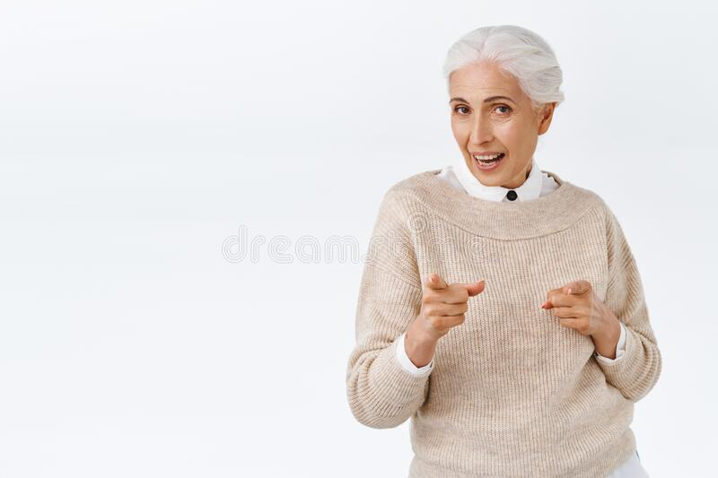 Elegant, positive and active happy stylish senior lady office worker, pointing camera congratulate someone or greeting stock photos