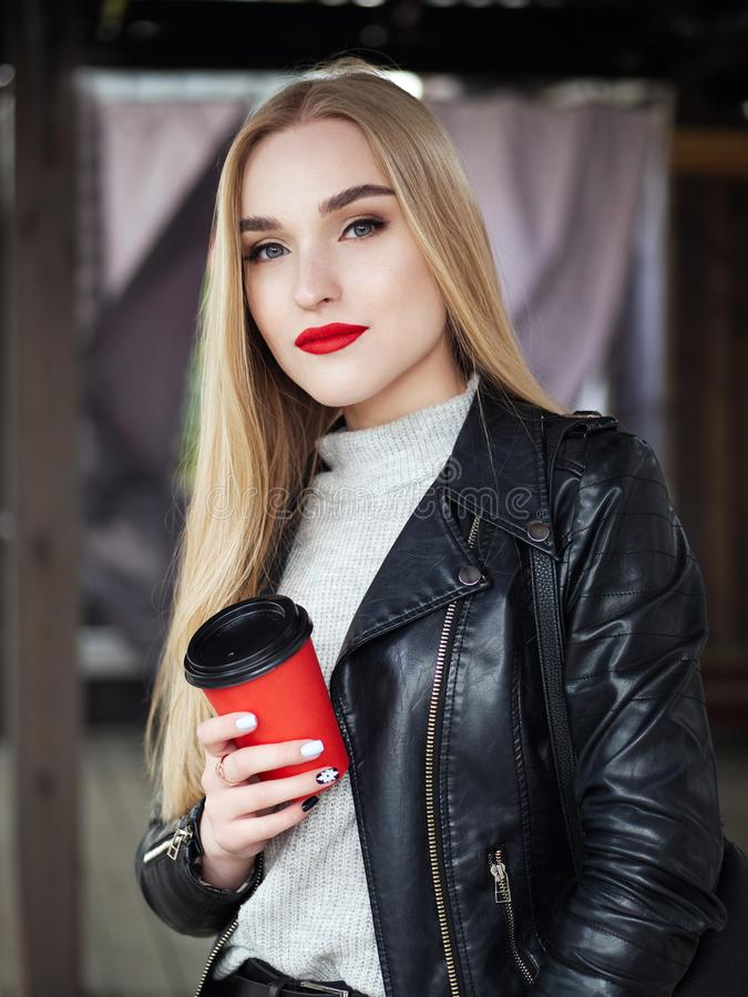 Elegant positive blond woman with trendy makeup bright vibrant red lips in leather coat drinking coffee from red disposable cup stock image