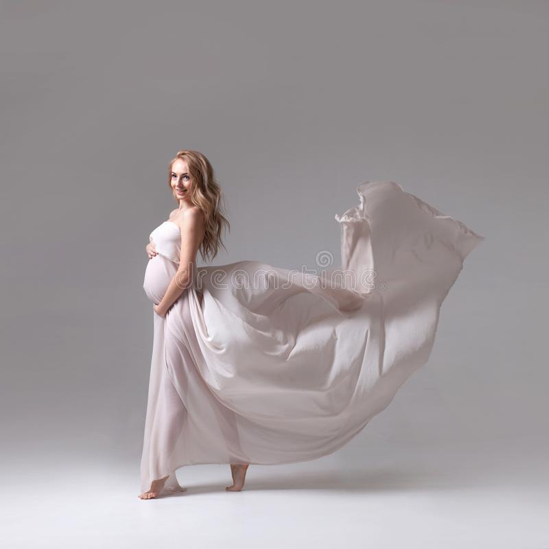Elegant pregnant woman in a white flying dress stock photos