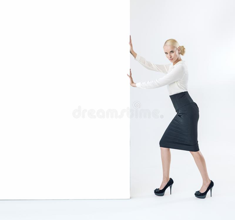 Elegant, pretty businesswoman puhing an empty board stock image