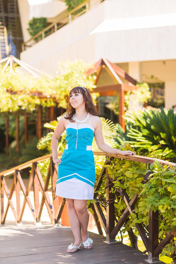 Elegant pretty slim woman posing near luxury resort near the beach royalty free stock image