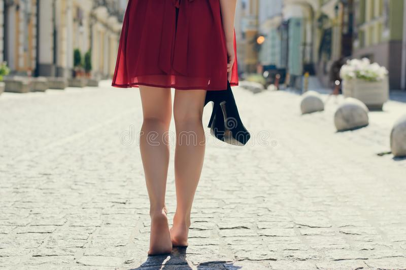 Elegant pretty woman with shoes in hands tired because of wearing high-heels walking along the street barefoot; close up photo royalty free stock images