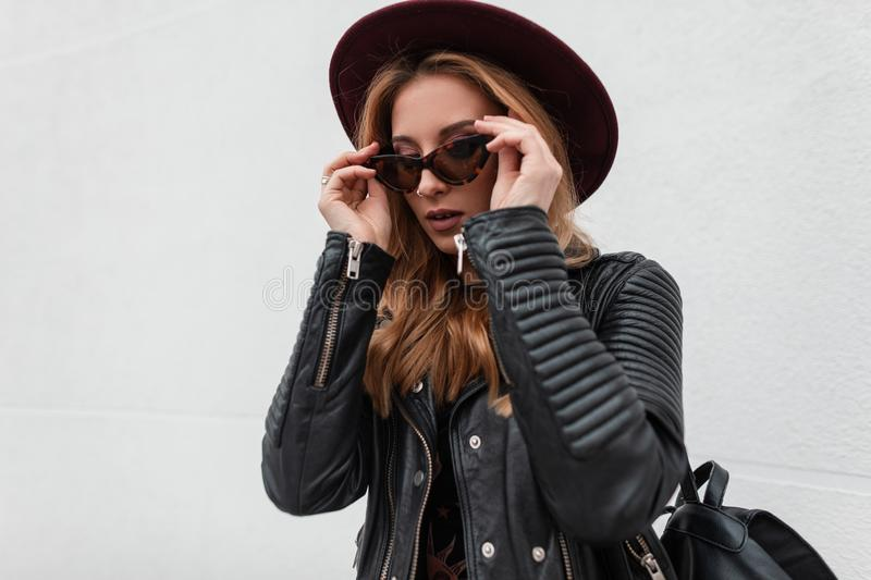 Elegant pretty young hipster woman in a vintage hat in stylish sunglasses in a fashionable black leather jacket with a backpack. Poses near a white wall in the royalty free stock image