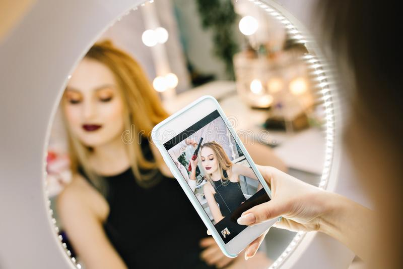 Elegant pretty young woman making photo on phone in mirror during making hairstyle in hairdresser salon. Stylish stock photography