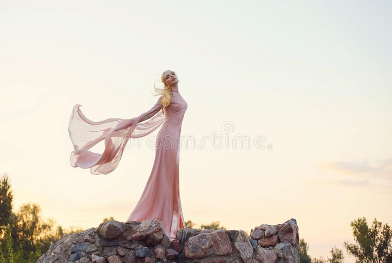 Elegant princess with blond fair wavy hair with tiara on it, wearing a long light pink rose fluttering dress, standing. On the tower of the castle at the sunset stock photography