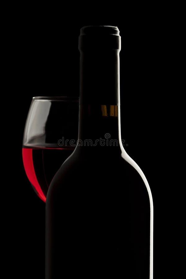 Elegant rött vinflaska och vinexponeringsglas royaltyfri fotografi
