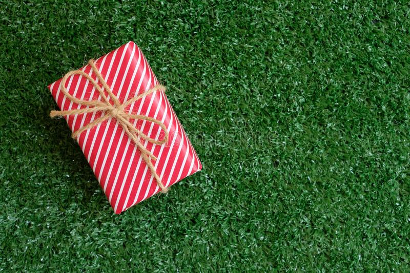 Elegant red gift box decorated green lawn background, valentine love present concept. Copy space passion heart day wrap mini pink vibrant saturated tag card royalty free stock image