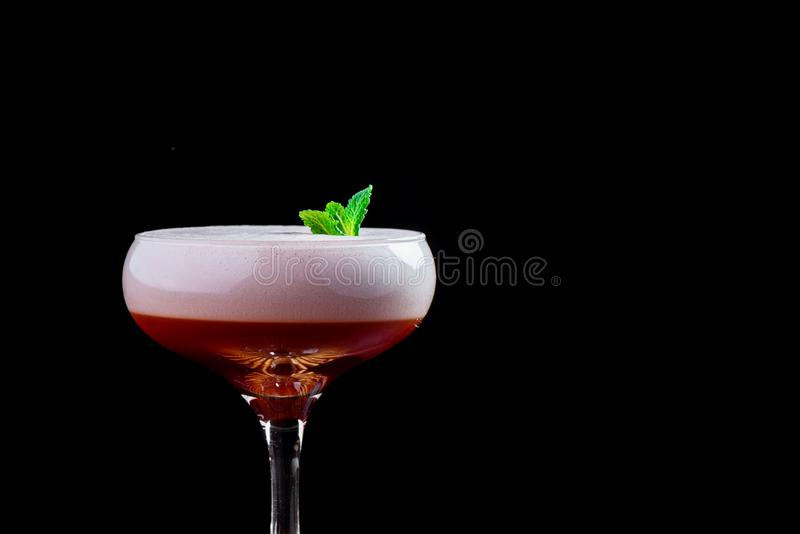 Elegant red ladies` cocktail with pink foam in a beautiful glass on a wooden carved round board stock photo