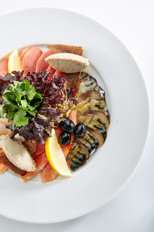 Elegant Restaurant Plate with Fish Delicacies. Top View. Smoked Butter Fish, Salmon, Perch, Marinated Dorado, Forshmak with Lemon, Olives, Quail Egg, Greens and stock image