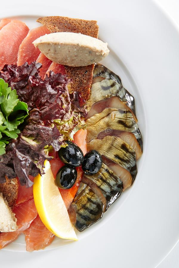 Elegant Restaurant Plate with Fish Delicacies. Top View. Smoked Butter Fish, Salmon, Perch, Marinated Dorado, Forshmak with Lemon, Olives, Quail Egg, Greens and stock photo