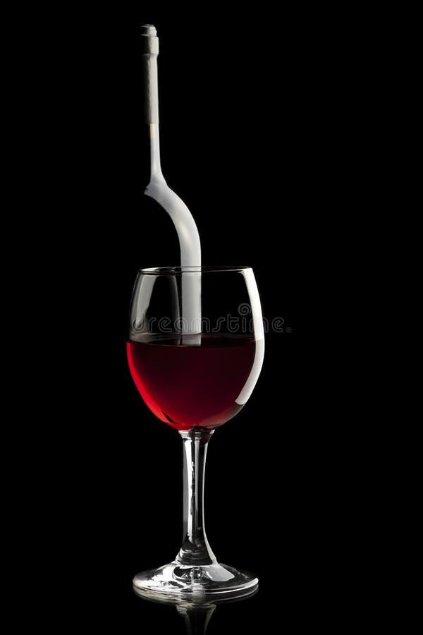 Elegant rode wijnglas en een wijnfles royalty-vrije stock foto's