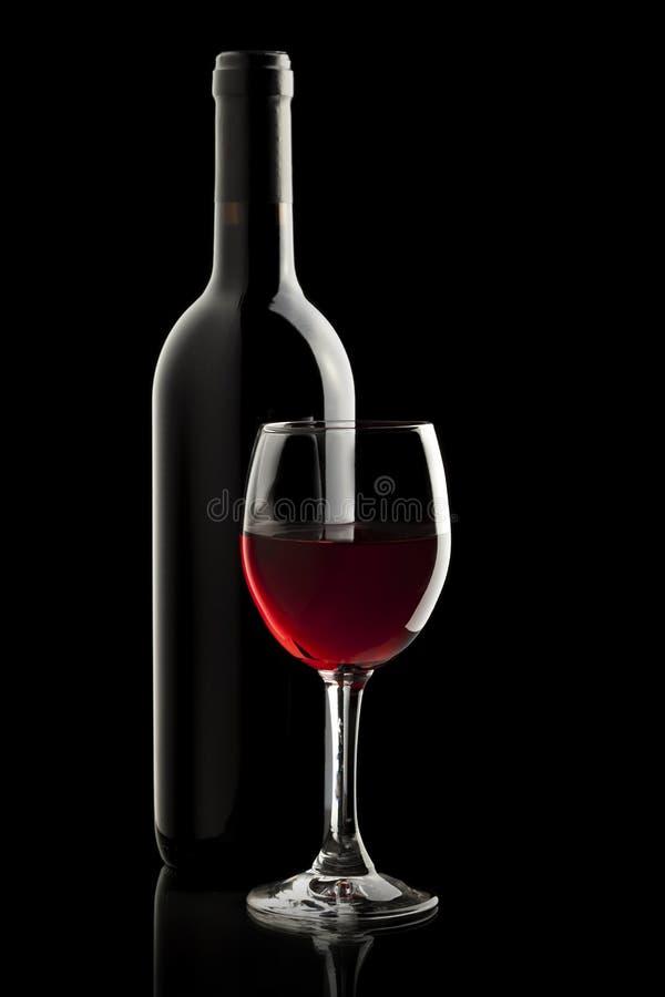 Elegant rode wijnglas en een wijnfles stock foto's