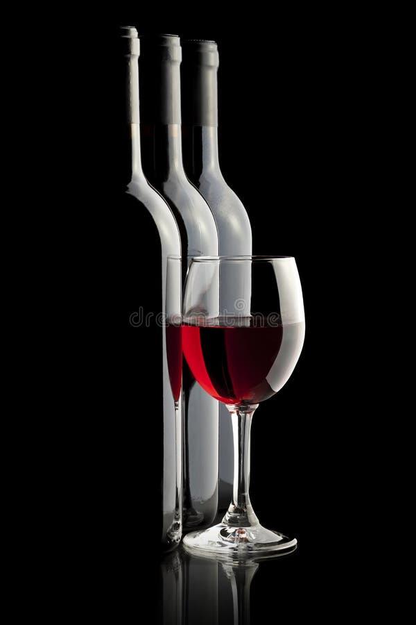 Elegant rode wijnglas en een wijnflessen royalty-vrije stock fotografie
