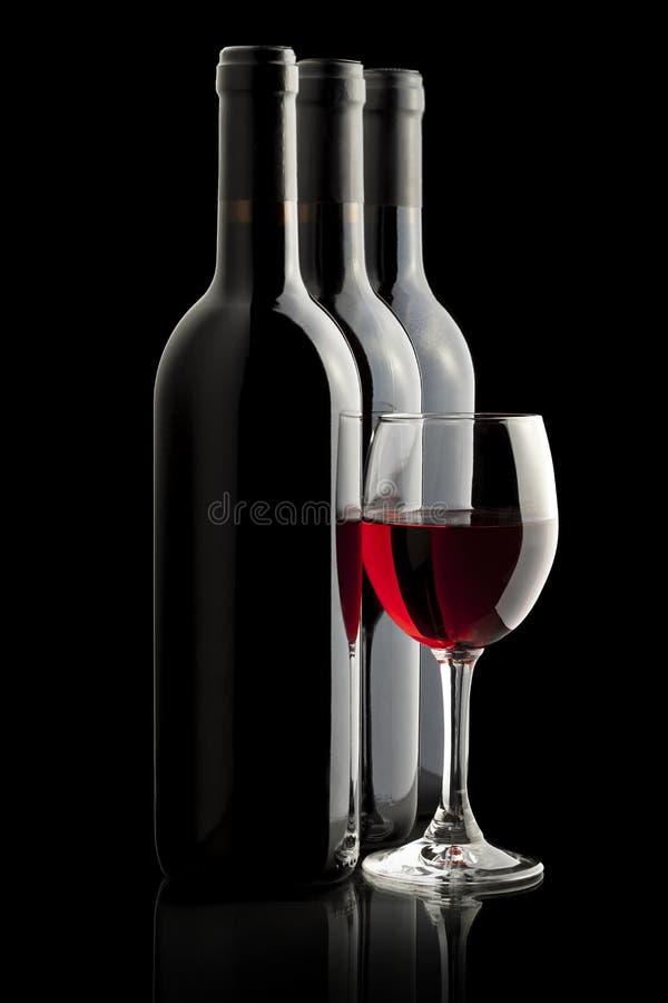 Elegant rode wijnglas en een wijnflessen stock fotografie