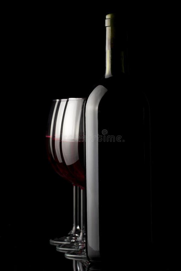 Elegant rode wijnglas en een wijnflessen stock afbeelding