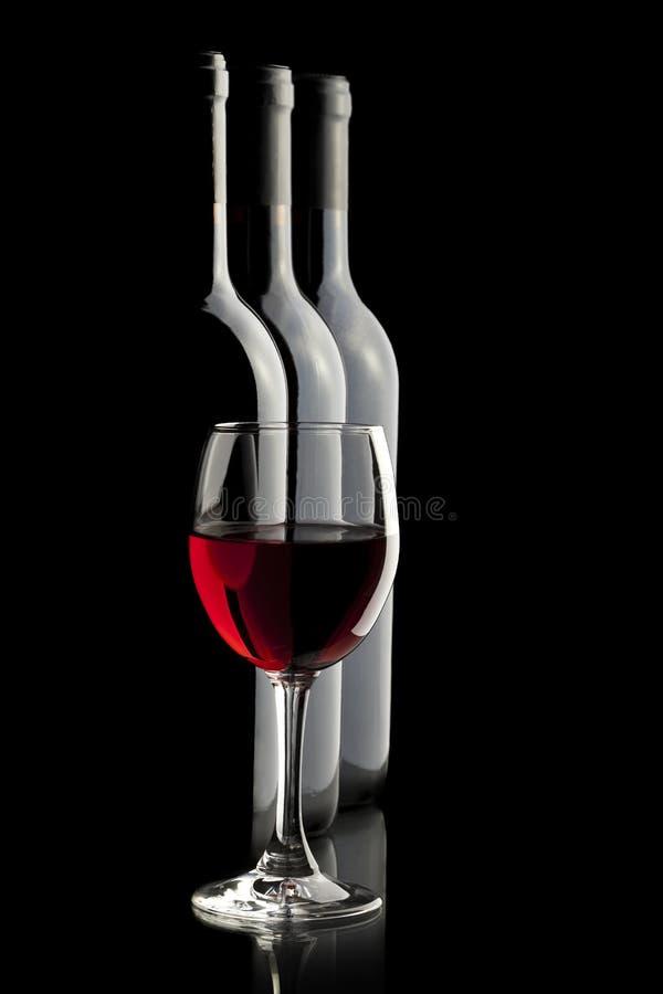 Elegant rode wijnglas en een wijnflessen royalty-vrije stock foto