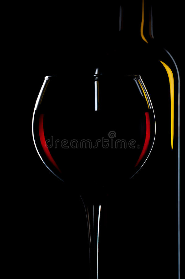 Elegant rode wijnglas en een wijnflessen op zwarte achtergrond royalty-vrije stock fotografie