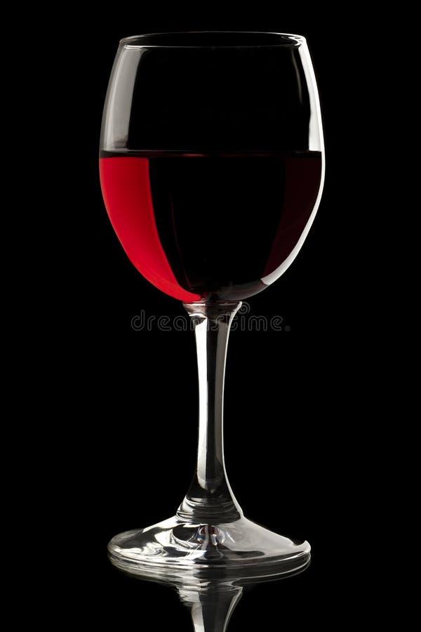 Elegant rode wijnglas op zwarte achtergrond stock afbeelding