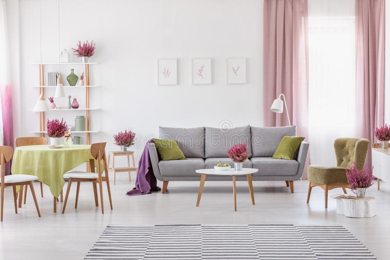 Elegant daily room with round table with wooden chairs and grey sofa with olive green pillows, stylish armchair next to it stock photo