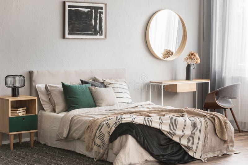 Elegant rund spegel i träram ovanför den utsmyckade konsoltabellen med blommor i vas i det moderiktiga sovrummet som är inre med  arkivfoto