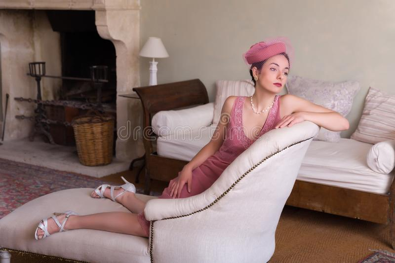 Elegant 20s woman on chaise-longue. Sensual 1920s woman in pink flapper dress sitting on an antique chaisee longue or recliner royalty free stock images