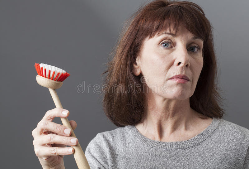 Elegant 50s woman handing over dish brush for washing and cleaning at home stock photo