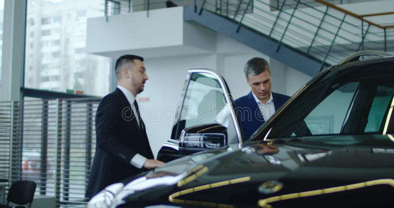 Salesman inviting potential buyer to get in car. Elegant salesman inviting potential buyer to get in the car in showroom royalty free stock photo