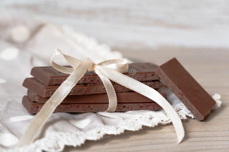 Elegant sammansättning av mjölkar choklad med ett band och en pilbåge på bordduken arkivbild
