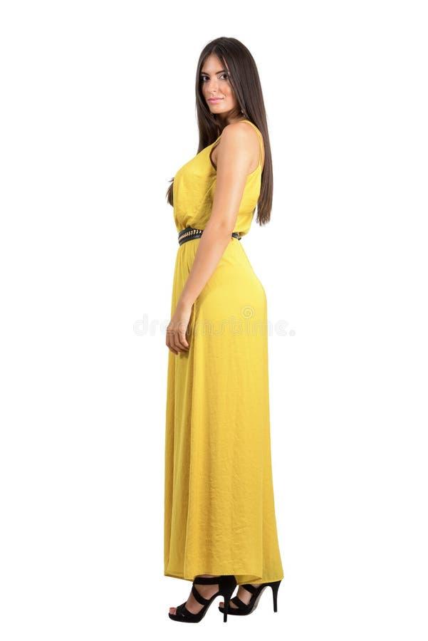Elegant schoonheidsmodel in geel avondjurk zijaanzicht royalty-vrije stock afbeeldingen