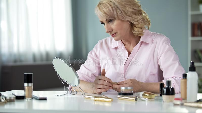 Elegant senior lady looking in mirror on table, anti-wrinkle collagen cosmetics. Stock photo royalty free stock photography