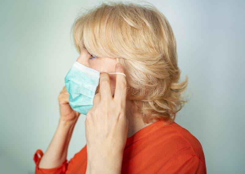 Elegant senior woman putting properly surgical mask royalty free stock photos