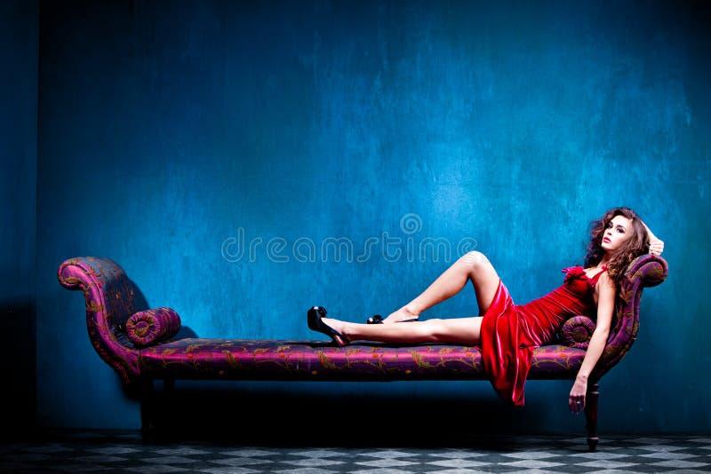 Elegant sensual woman. Sensual elegant young woman in red dress on recamier indoor shot