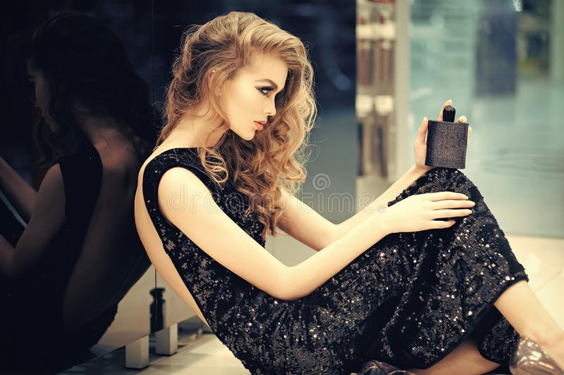 Elegant sensual young woman holding perfume royalty free stock images
