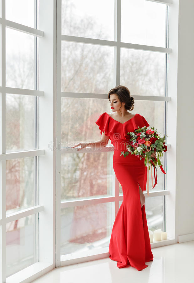 Elegant sexig brunettflicka i en röd klänning med en krans och en bo royaltyfria bilder