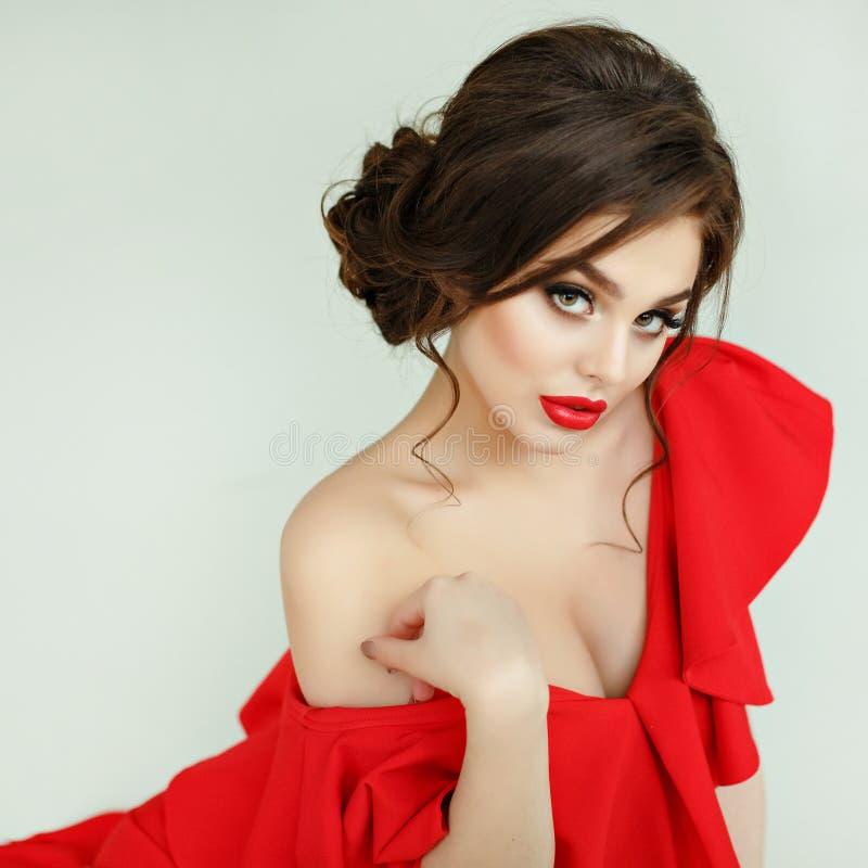 Elegant sexig brunettflicka i en röd klänning som ligger på golvet, st royaltyfri fotografi