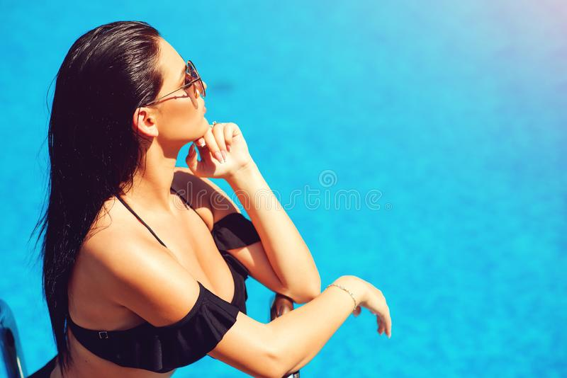 Elegant sexy woman in the black bikini on the sun-tanned slim and shapely body is posing near the swimming pool. Sensual girl in stock image