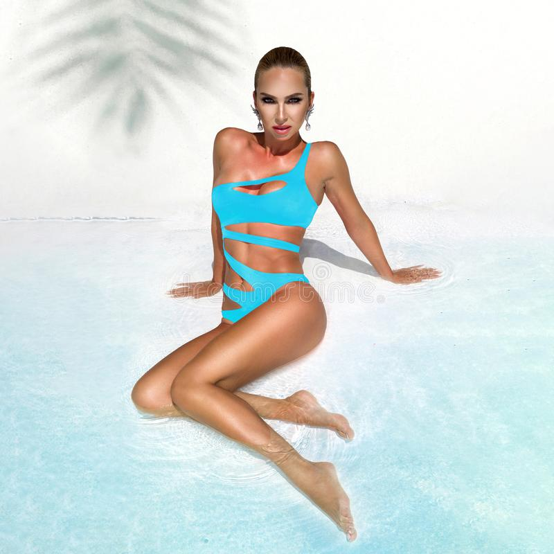 Elegant sexy woman in the blue bikini on the sun-tanned slim and shapely body is posing near the swimming pool - Image. Elegant sexy woman model in the blue royalty free stock photo