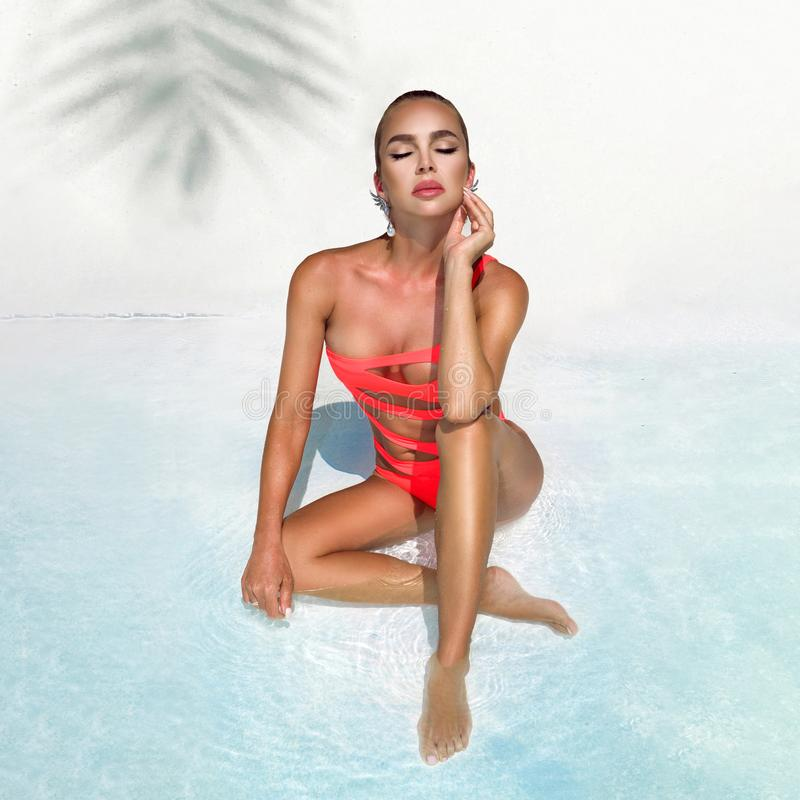 Elegant sexy woman in the orange bikini on the sun-tanned slim and shapely body is posing near the swimming pool - Image royalty free stock photos